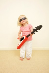 Toddler wearing sunglasses, playing guitar